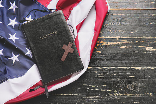 Holy Bible, cross and USA flag on wooden background