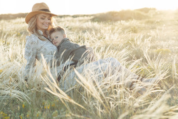 Mom with a child have fun playing in nature. A pregnant woman and a child are resting in nature.