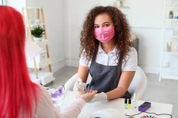 Manicure master working with female client in beauty salon