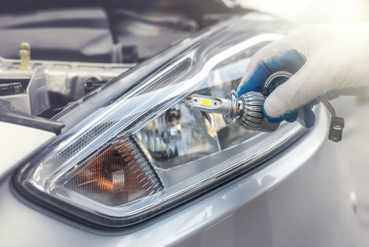 male's hand holding light bulb of car headlight for repair auto