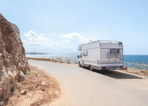 Motor Home On Road By Sea Against Sky During Sunny Day