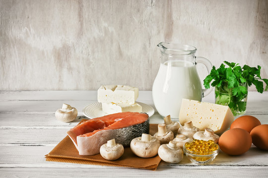 Vitamin D rich foods on a white wooden table. Natural sources of vitamin D are dairy products, salmon, egg, mushrooms, parsley, fish oil.
