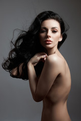 Sexy fashion nude woman with long hair, curly strong hair of a brunette girl. Natural cosmetics for...