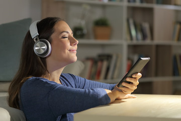 Girl listens music on phone with headphones at night