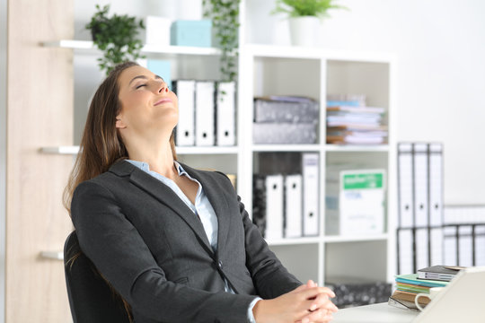 Executive woman breathing fresh air sitting at office