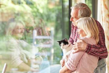 Glückliches Paar Senioren schaut aus dem Fenster