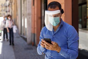 Uomo moro con camicia blu mascherina chirurgica e maschera professionale parla al telefono in una via del centro Wall mural