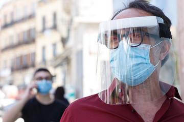 Uomo con mascherina protettiva e maschera in plexiglass professionale  è poggiato sulla vetrina di...