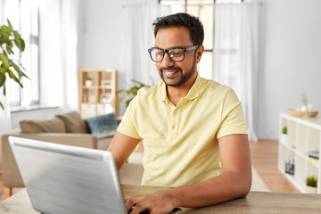 technology, remote job and lifestyle concept - happy indian man in glasses with laptop computer working at home office