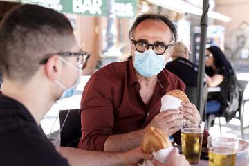 un uomo e un ragazzo mangiano un panino seduti nel tavolino di un bar protetti dalla mascherina...