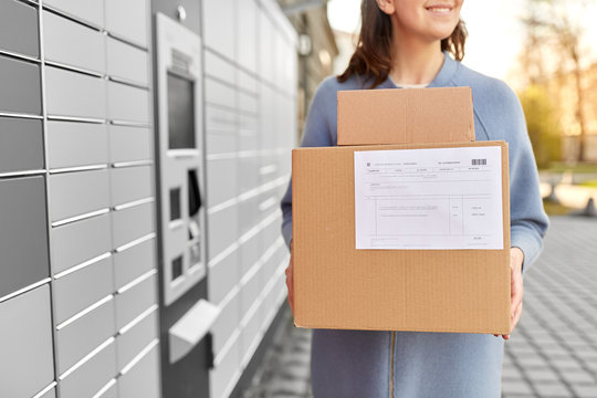 mail delivery and post service concept - close up of happy smiling woman with boxes at outdoor automated parcel machine