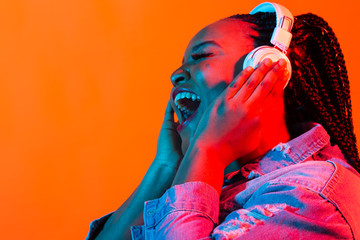 Young african-american woman listening to music in headphones in neon light. Female portrait....