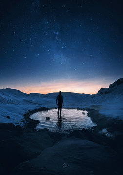 Traveler stands in a secret hot spring at night in Iceland under the breathtaking starry sky with the Milky Way