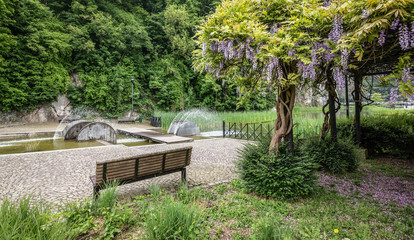 Empty bench in the park with a wisteria plant and a modern water fountain near the city center of Durbuy in the Belgian Ardennes.