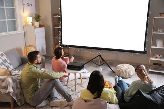Young friends watching movie at home