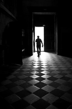 Silhouette Man Walking On Checked Pattern In Room