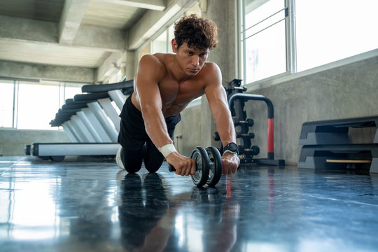 Athletic man exercising with fitness roller in gym club,Athlete builder muscles concept.