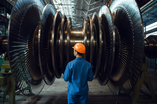 Worker checks turbine impeller vanes on factory