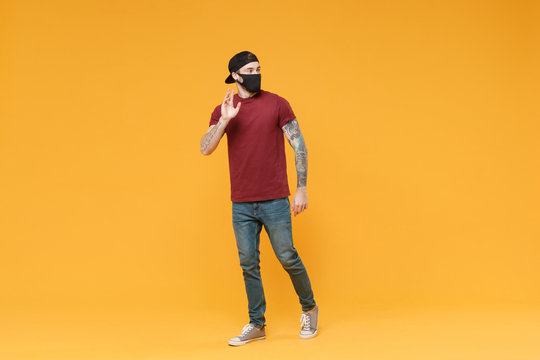 Young tattooed man guy in casual t-shirt cap black face mask posing isolated on yellow background studio. People lifestyle concept. Mock up copy space. Waving greeting with hand as notices someone.