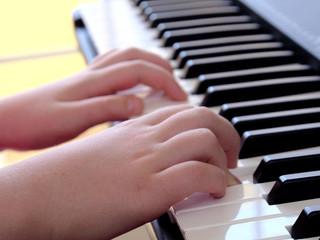 Closeup girl hands playing piano