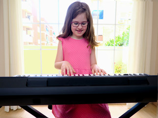 Young girl playing electronic piano at home