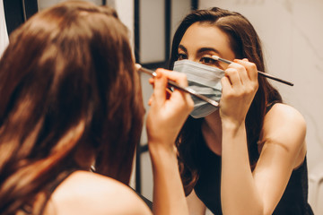 selective focus of young woman in medical mask and black dress applying eye shadow in bathroom