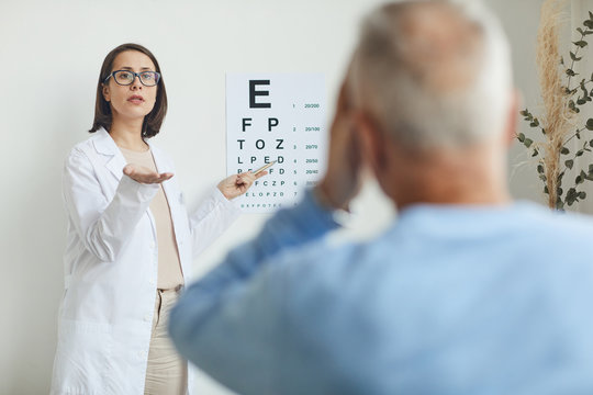 Waist up portrait of young female ophthalmologist pointing at eye chart while testing eyesight of senior patient, copy space