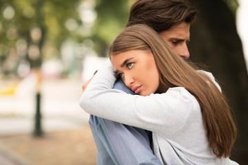 Keuken foto achterwand Honden Unhappy Girl Hugging Unloved Boyfriend Standing Outdoors In Park