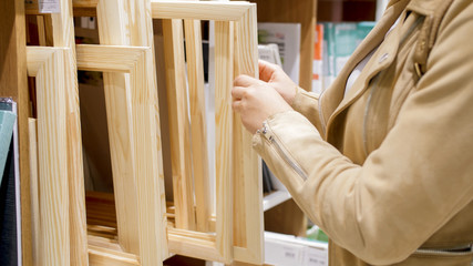 Wall Murals Stairs Closeup image of young female artist choosing wooden frame in hobby store
