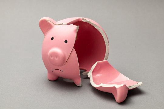 Broken piggy bank on gray background
