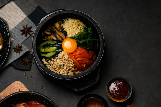 Korean Food Style : Top view of bibimbap or pibimpap in the black bowl. The main ingredients are yolk egg , Shiitake mushrooms, minced chicken, bean sprouts, cucumbers, carrots and pickles with rice