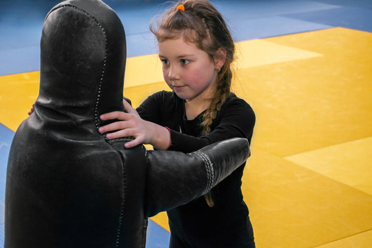 The child trains in the wrestling hall. The child is practicing fighting techniques on the simulator in the gym. The little girl is engaged in martial arts with a training manikin.