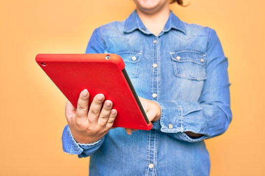 Young caucasian woman working using tablet standing over isolated yellow background