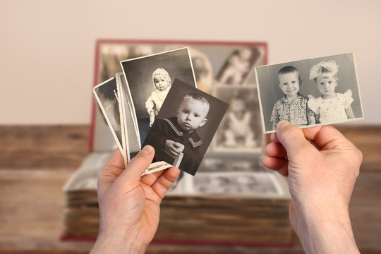 male hands hold old retro family photos over an album with vintage monochrome photographs in sepia color and wooden toy clown, genealogy concept, ancestral memory, family ties, childhood memories