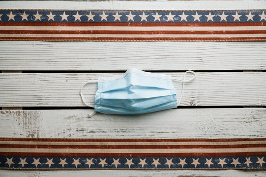 American stars and stripes flat lay over rustic wood background 4th of July memorial day in Americana style. With Covid mask