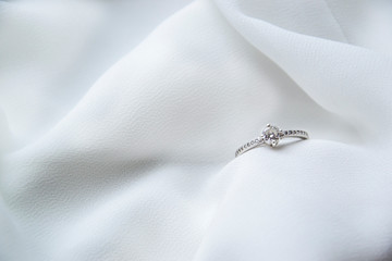 Macro picture of engagement ring on the side on white silky background as wedding card fashion concept background wallpaper with gift for her to say yes in romantic time as fashion style