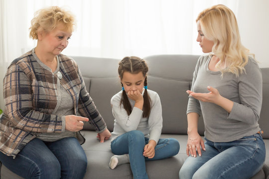 Little girl sitting at home crying while mom and granny scolding her