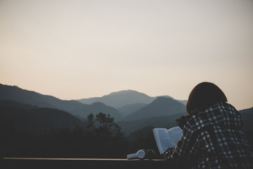 Young woman sitting reading a book at nature in the evening.