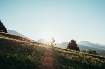 Young athletic man on MTB e-bike pedaling up the hill with green grass on a sunset/sunrise. Alone in nature, thinking about life and exploring the world with a bike. Morning light.