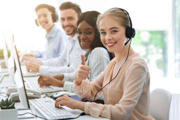 Multiethnic call centre consultants with headsets smiling at camera in office