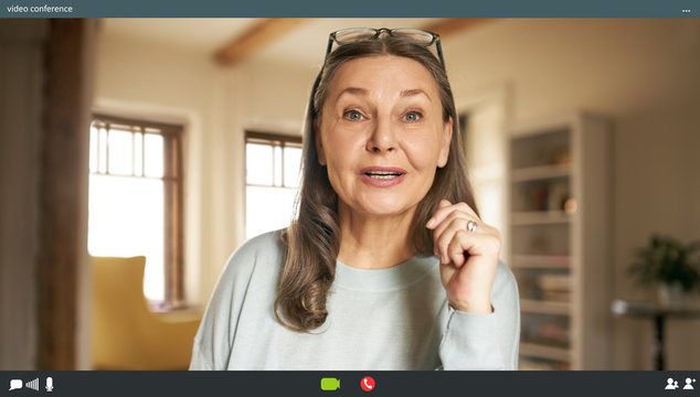 Portrait of casually dressed energetic elderly woman with loose gray hair posing in stylish apartment interior looking at camera with mouth opened, speaking via virtual chat, making webcam video call