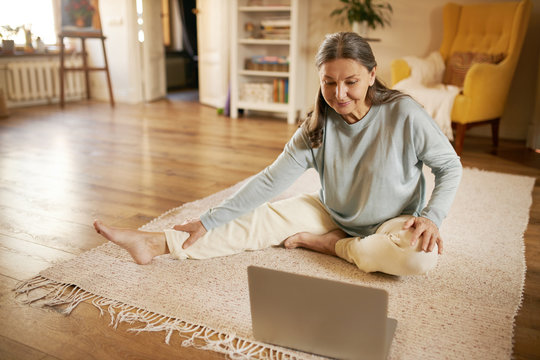 Online training, technology, health and activity. Happy active barefoot mature woman sitting on floor in front of open laptop, doing yoga, repeating exercises after professional instructor on video