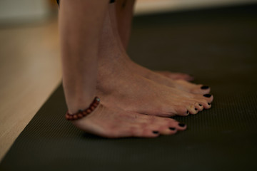 Closeup of woman standing on the mat and doing yoga stretching.