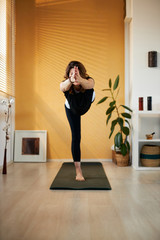 Attractive fit smiling middle aged yogi woman standing on mat in Lord of the Dance yoga pose at home.