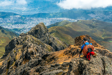 A mountain climber with ropes and walking sticks enjoying the view and making a phone call after reaching the Rucu Pichincha Volcano Peak, Quito, Ecuador.