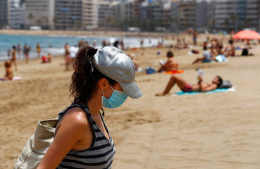 A woman with a face mask leaves the Las Canteras beach as some Spanish provinces are allowed to ease lockdown restrictions during phase two, on the island of Gran Canaria