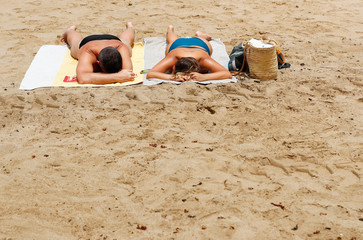 Two people sunbathe in the Las Canteras beach as some Spanish provinces are allowed to ease lockdown restrictions during phase two, on the island of Gran Canaria