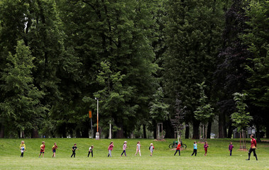 Children exercise in a park in Prague