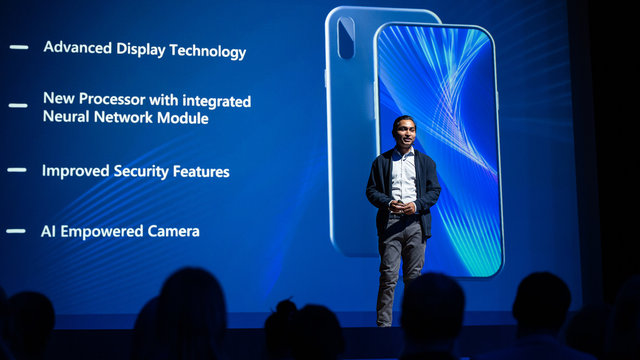 Live Event with New Products Reveal: Keynote Speaker Presents Smartphone Device to Audience. Movie Theater Screen Shows Mock-up Touch Screen Mobile Phone with High End Features and Top Highlights