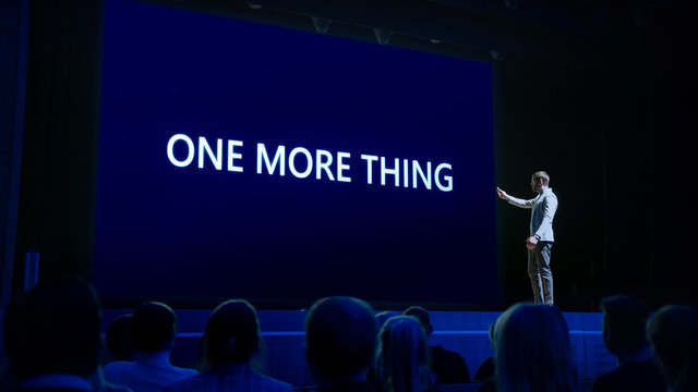 Live Event with Brand New Products Reveal: Keynote Speaker Presents New Device to Audience. Movie Theater Screen Shows Text -one more thing-